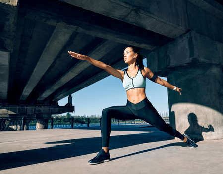 Young sporty woman doing yoga asana Warrior I Pose outdoors under industrial bridge. Practicing yoga, wellbeing and healthy lifestyle. Virabhadrasana