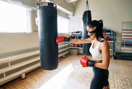 Female boxer hitting a huge punching bag at fitness gym. Woman practicing her punches at a boxing studio