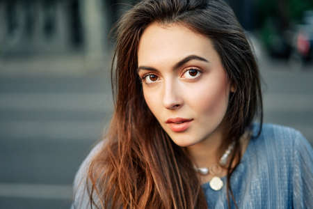 Close up young beautiful woman portrait posing in the city street in summer