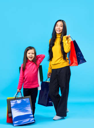 Happy mother with adorable little daughter holding shopping bags enjoy their purchase on blue background. Fun, sale, family concept