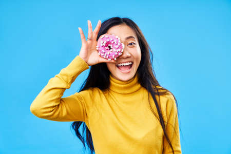 Attractive woman having fun with donuts. Girl showing doughnuts in front of her eyes on blue background. Tasty food, diet concept