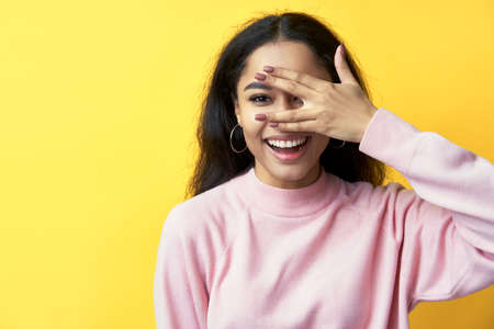 Smiling black woman looking through fingers clothing eyes with hand