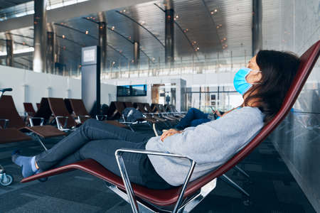 Woman in virus protection face mask rest and sleep in the departure airport lounge