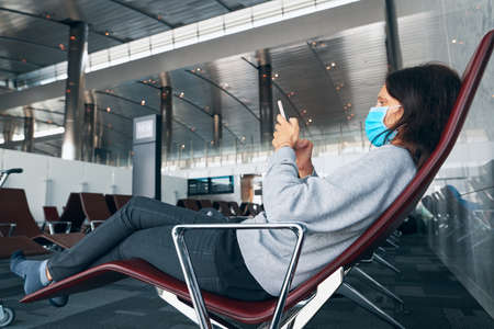 Woman in virus protection face mask rest with smartphone in the departure airport lounge