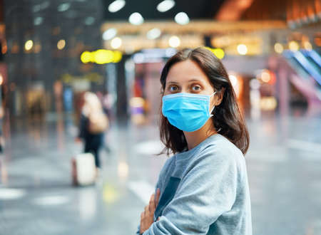 Traveler woman in virus protection face mask in international airport