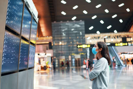 Woman in virus protection face mask looking at information board checking her flight in international airport