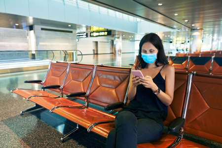 Woman in virus protection face mask using a smartphone sitting in empty airport
