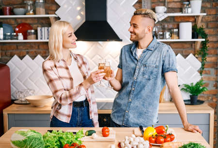 Young happy couple drinking champagne and enjoying the company of each other in kitchen at home
