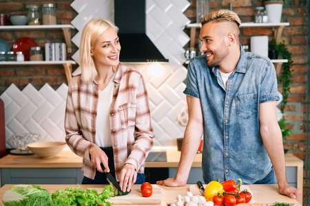 Smiling young couple cooking together vegetarian meal in the kitchen at home