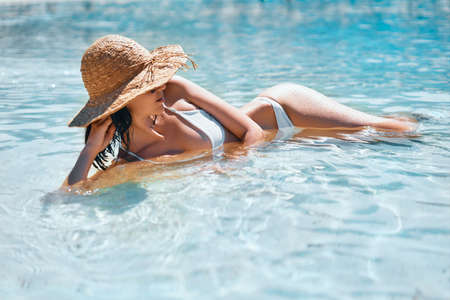 Young woman in straw hat and white bikini relax in turquoise sea on tropical paradise beach Reklamní fotografie