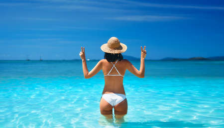 Happy sexy woman in white bikini and straw hat showing peace sign with both hands relax in turquoise sea Reklamní fotografie