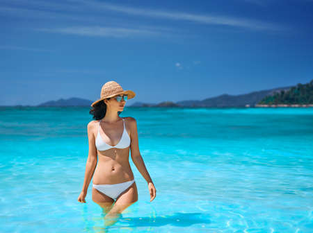 Sexy young woman in straw hat and white bikini on tropical paradise beach