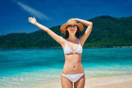 Young happy woman in white bikini and straw hat raised hands up enjoy her summer vacation