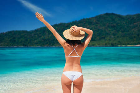 Back view of young happy woman in white bikini and straw hat raised hand up enjoy her summer vacation on tropical beach Reklamní fotografie