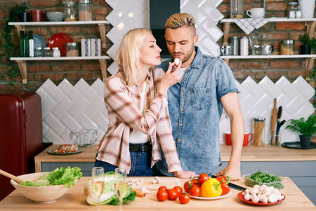 Young man refuse to eat vegetables. Woman feeding man with healthy food while cooking in kitchen