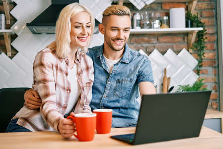 Happy couple drink coffee and using laptop relax together at their kitchen Foto de archivo