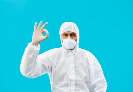Doctor in protective medical suit showing ok sign isolated on blue background