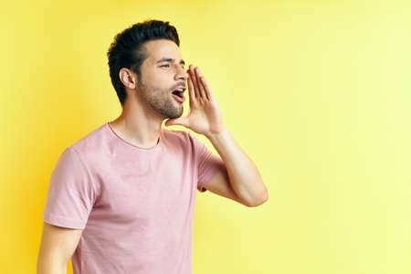 Young handsome man shouting and screaming loud to side with hand on mouth and copy space for text Stock Photo
