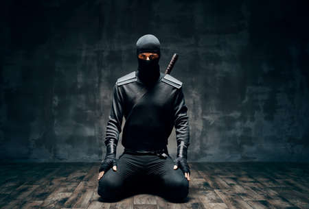 Ninja kneeling posing with a sword over black background