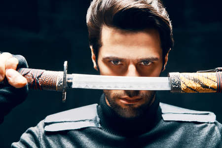 Warrior man posing with a sword Stock Photo