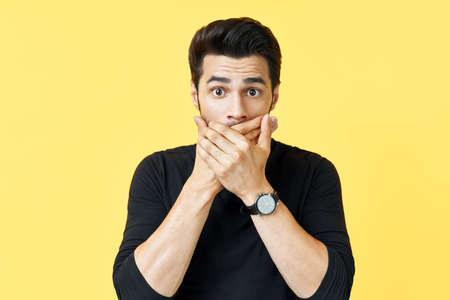 Shocked man covering mouth with hands over yellow background.