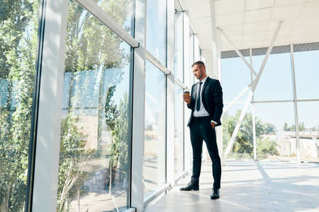 Full length portrait of elegant businessman with cup of coffee in hand during break time in modern office with copy space