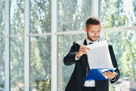 Confident handsome businessman with clipboard working on documents in a bright modern office with copy space