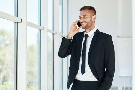 Smiling handsome businessman talking on phone in open space modern office with panoramic windows background