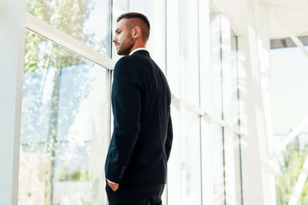 Confident businessman in elegant suite in modern creative office looking in panoramic windows