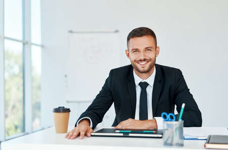 Stylish smiling businessman in elegant suit sitting at his desk in a bright modern office 免版税图像