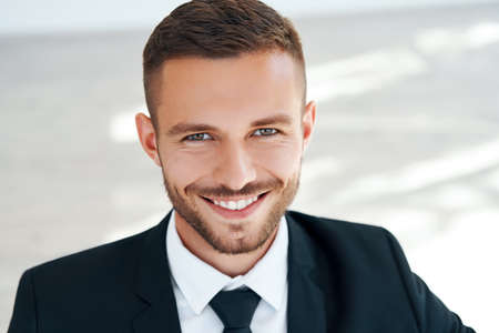 Close up portrait of handsome smiling young man in elegant suit