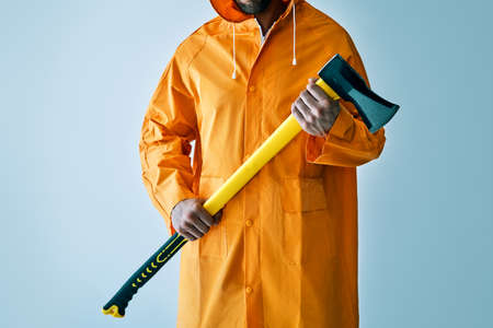 Cropped image of man in bright raincoat holding big axe
