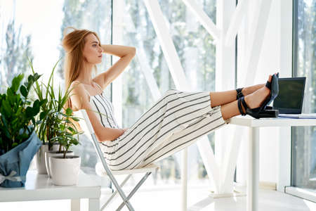 Pretty young businesswoman relaxing in modern office with legs on the table enjoying free time