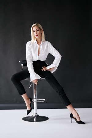 Full length fashion portrait of young stylish woman posing on black background.