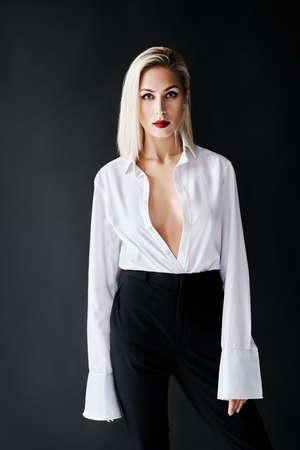 Fashion portrait of sexy trendy woman posing on black studio background.