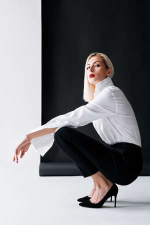 Sexy blonde woman with red lips wearing white shirt and black classic pants posing on black studio background