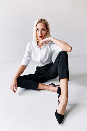 Portrait of daring trendy woman posing on white studio background. sitting on floor Stock fotó