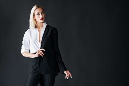 Young stylish woman wearing classic mens suit posing on black studio background with copy space