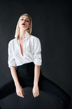Fashion portrait of sexy trendy woman posing on black studio background