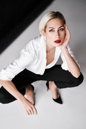 Top view portrait of daring trendy woman posing on white studio background sitting on floor Stock fotó