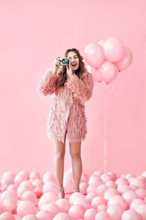 Pretty happy glamour woman taking photo with retro camera over pink background Archivio Fotografico