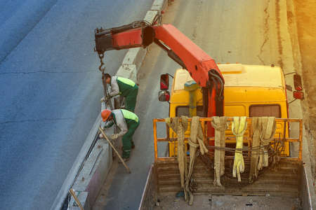 two workers install concrete fence along the road Stock Photo