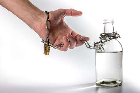 hand tied metal chain with bottle on white background. alcohol dependence