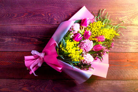 bouquet with Mimosa, hyacinths and tulips in pink packaging on a wooden table