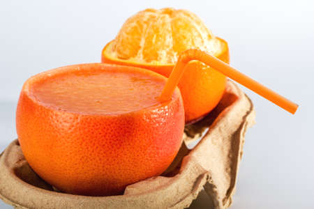 orange juice in the orange peel and the peeled orange on a cardboard tray