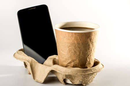 smartphone and black coffee in a cardboard Cup together on a cardboard tray under the glasses