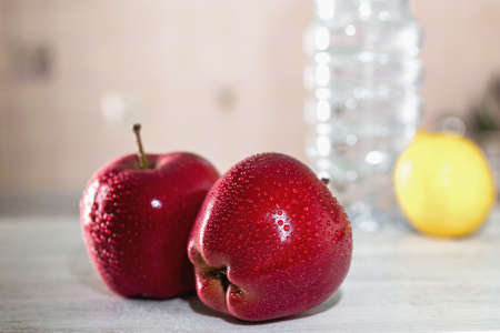 two red apples on a white table, next to a bottle of water and lemon