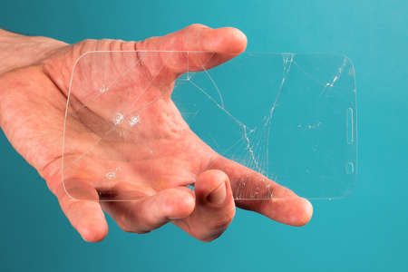 man holds broken, broken smartphone safety glass in his hand on blue background. concept of fragile equipment