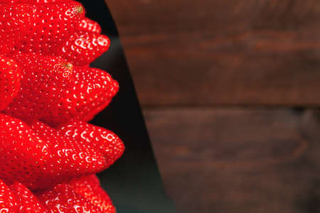 bouquet of red strawberries in a black wrapper on wooden background. near place for text
