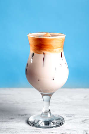 Iced Dalgona Coffee, a trendy fluffy creamy whipped coffee on bright blue background. new trends in coffee